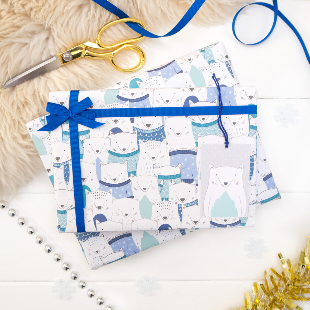 A parade of arctic foxes wearing a variety of woolly jumpers printed onto white gift wrap. Matching fox tag shown on the bottom right of the wrapping paper. The present is strung with blue ribbon and features a small bow.