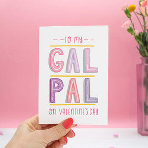 To my Gal Pal on Valentine's Day. A friendship card designed for Valentine's or Galentine's day! The image features my hand lettered card held in my left hand and with a vase of roses on a pink background