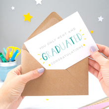 Load image into Gallery viewer, You only went and graduated congratulations card being pulled from an envelope by Joanne Hawker in front of a grey background with white and yellow stars. The typography is a mix of grey and varying tones of blue.