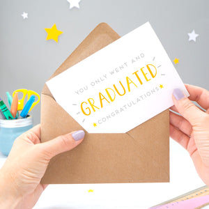 You only went and graduated congratulations card being pulled from an envelope by Joanne Hawker in front of a grey background with white and yellow stars. The typography is a mix of grey and varying tones of yellow and orange.