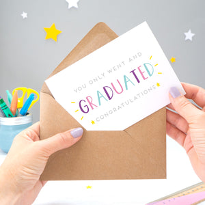 You only went and graduated congratulations card being pulled from an envelope by Joanne Hawker in front of a grey background with white and yellow stars. The typography is a mix of grey and varying tones of blue, pink and purple.