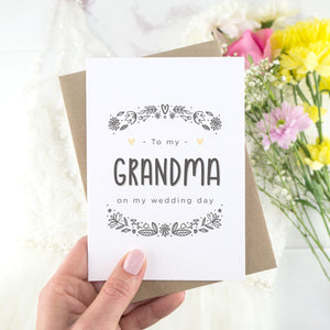 To my grandma on my wedding day. A white card with grey hand drawn lettering, and a grey floral border. The image features a wedding dress and bouquet of flowers.