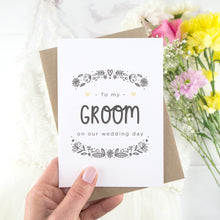 Load image into Gallery viewer, To my groom on our wedding day. A white card with grey hand drawn lettering, and a grey floral border. The image features a wedding dress and bouquet of flowers.