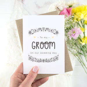 To my groom on our wedding day. A white card with grey hand drawn lettering, and a grey floral border. The image features a wedding dress and bouquet of flowers.