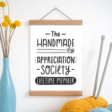The handmade appreciation society print in black and white and held in a magnetic frame next to a vase of yellow flowers and wool with knitting needles.