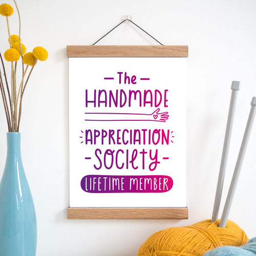The handmade appreciation society print in purple and pink ombre and held in a magnetic frame next to a vase of yellow flowers and wool with knitting needles.
