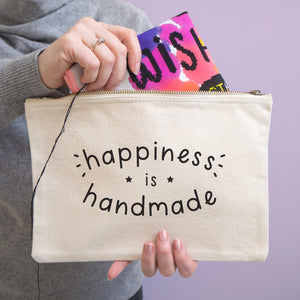 Happiness is handmade large natural project pouch being held in front of a purple background with a cross stitch being pulled out of the pouch.