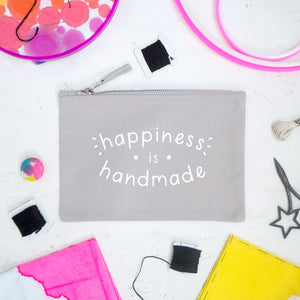 Happiness is handmade medium grey pouch lying on a white wooden background surrounded by a stitchsperation cross stitch kit.