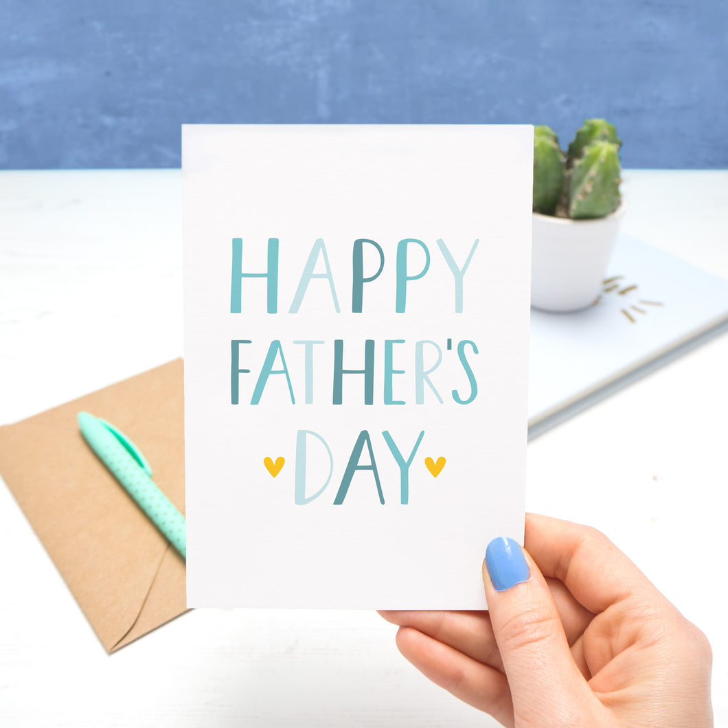 A very simple card that reads 'Happy Father's Day' held by Joanne Hawker in her Somerset Studio over a white and blue background. The text on the card is in varying shades of blue with two small yellow hearts around the word 'day'.