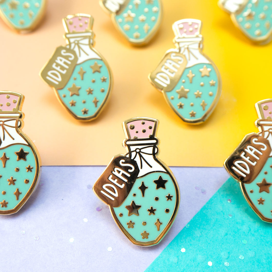 A potion bottle filled with teal and blue, sparkly new ideas in the form of a hard enamel pin