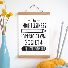 The indie business appreciation society print in black and white and held in a magnetic frame next to a vase of yellow flowers and wool with knitting needles.