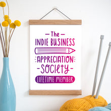 Load image into Gallery viewer, The indie business appreciation society print in pink and purple ombre and held in a magnetic frame next to a vase of yellow flowers and wool with knitting needles.