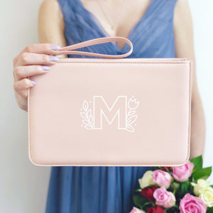 A pink, personalised Bridesmaids wristlet held by Joanne Hawker in a lilac bridesmaid dress with a bunch of pink and red roses. The wristlet features the floral monogram design in the letter M.