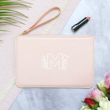 Load image into Gallery viewer, A pink personalised initial bridesmaid wristlet flat lay featuring the pouches lying on a grey background with lipstick, foliage and flowers used as props. The bag has a floral monogram letter M printed on the front.