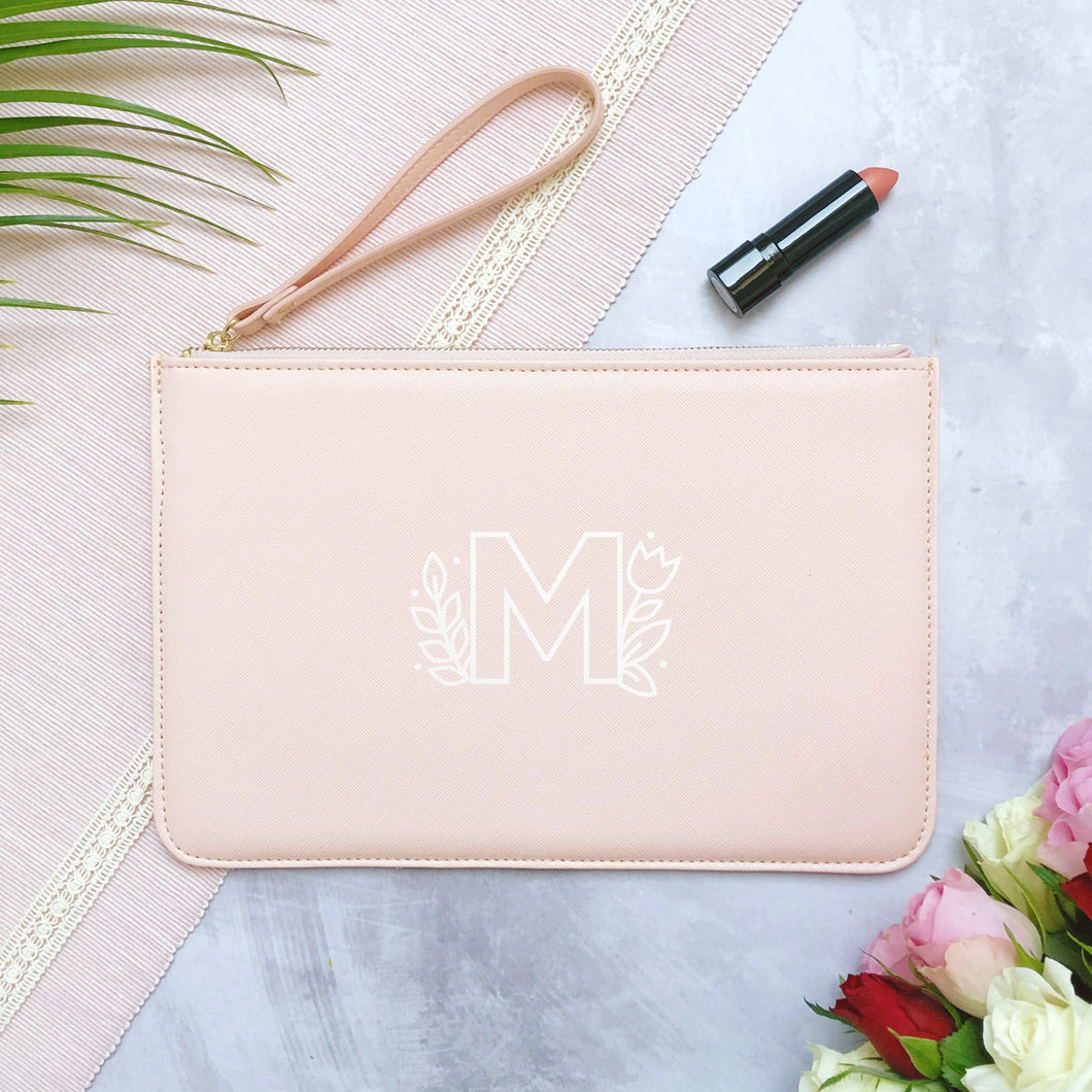 A pink personalised initial bridesmaid wristlet flat lay featuring the pouches lying on a grey background with lipstick, foliage and flowers used as props. The bag has a floral monogram letter M printed on the front.