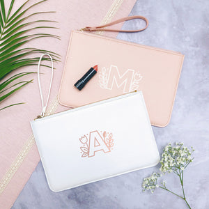 A white and pink personalised initial bridesmaid wristlet flat lay featuring the pouches lying on a grey background with lipstick, foliage and flowers used as props. These bags feature the initial monogram design in rose gold and white.