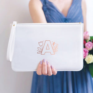 A white, personalised Bridesmaids wristlet held by Joanne Hawker in a lilac bridesmaid dress with a bunch of pink and red roses. The white wristlet features a rose gold floral monogram letter A
