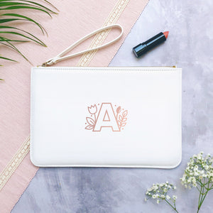 A white personalised initial bridesmaid wristlet flat lay featuring the pouches lying on a grey background with lipstick, foliage and flowers used as props. The white bag has a rose gold floral letter monogram A on the front.