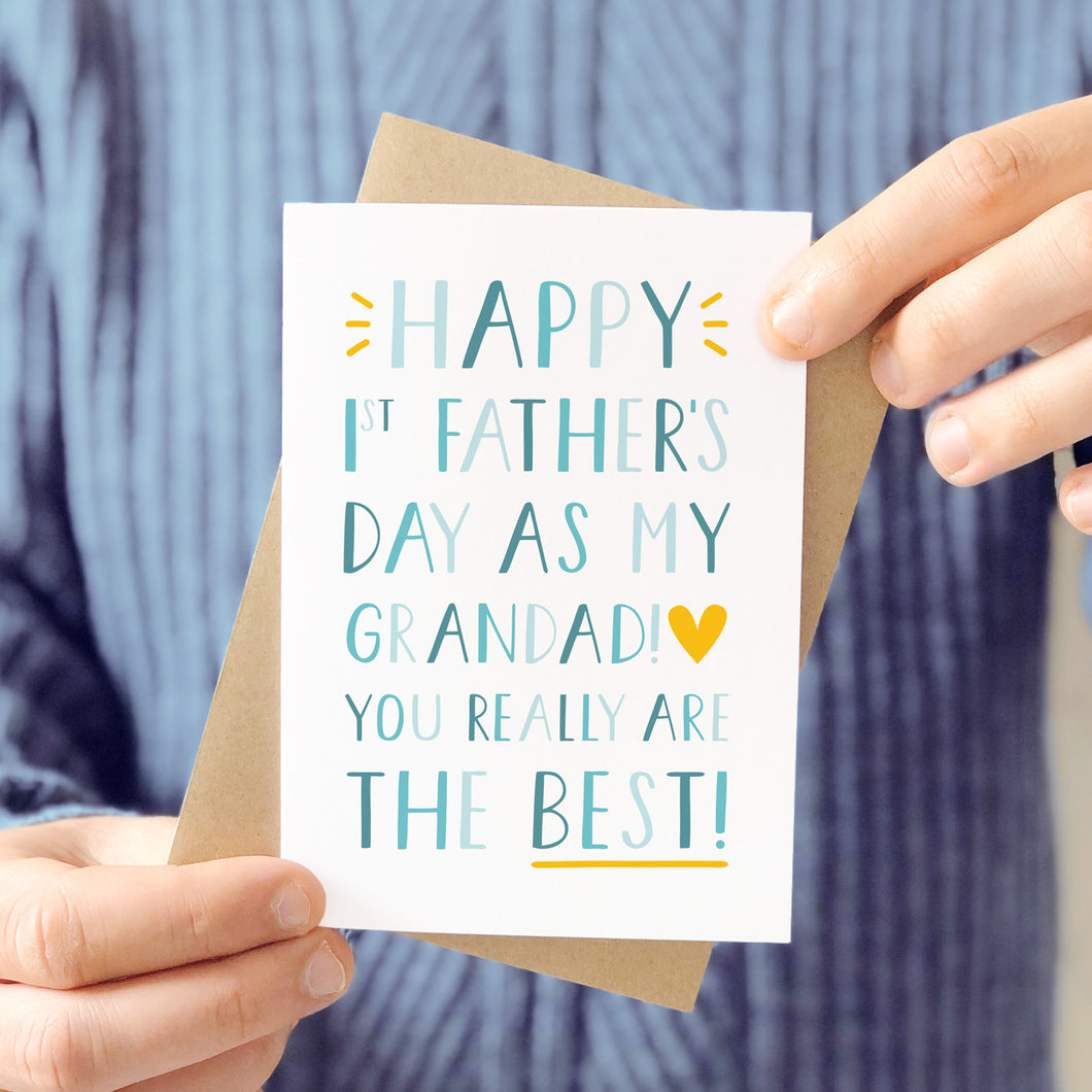 'Happy 1st Father's Day as my Grandad! You really are the best!' Photographed being held in front of a man wearing a grey blue knitted jumper and being held with it's kraft brown envelope.