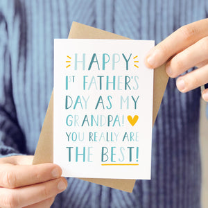 'Happy 1st Father's Day as my Grandpa! You really are the best!' Photographed being held in front of a man wearing a grey blue knitted jumper and being held with it's kraft brown envelope.