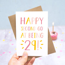 Load image into Gallery viewer, Happy second go at being 29 - milestone age card in pink photographed on a grey and blue background with a cupcake and burning candle.