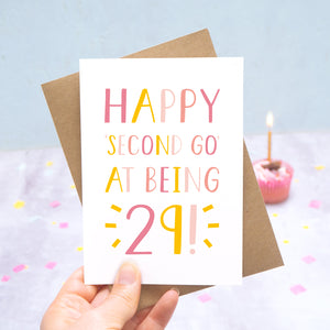 Happy second go at being 29 - milestone age card in pink photographed on a grey and blue background with a cupcake and burning candle.