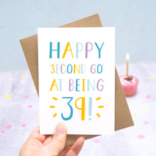 Load image into Gallery viewer, Happy second go at being 39 - milestone age card in blue, yellow and purple photographed on a grey and blue background with a cupcake and burning candle.