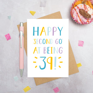 Happy second go at being 39 - milestone age card in blue, yellow and purple photographed on a grey background surrounded by a cupcake, pen and confetti.