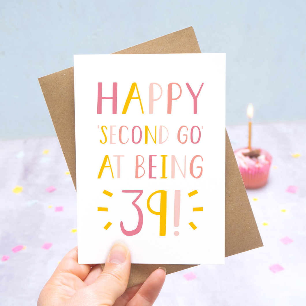 Happy second go at being 39 - milestone age card in pink photographed on a grey and blue background with a cupcake and burning candle.