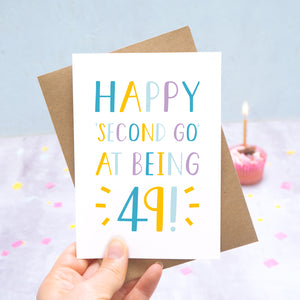 Happy second go at being 49 - milestone age card in blue, yellow and purple photographed on a grey and blue background with a cupcake and burning candle.