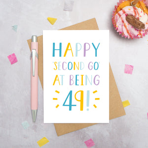 Happy second go at being 49 - milestone age card in blue, yellow and purple photographed on a grey background surrounded by a cupcake, pen and confetti.