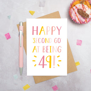 Happy second go at being 49 - milestone age card in pink photographed on a grey background surrounded by a cupcake, pen and confetti.