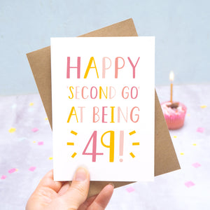 Happy second go at being 49 - milestone age card in pink photographed on a grey and blue background with a cupcake and burning candle.