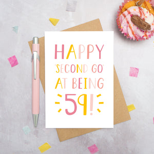 Happy second go at being 59 - milestone age card in pink photographed on a grey background surrounded by a cupcake, pen and confetti.