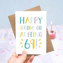 Load image into Gallery viewer, Happy second go at being 69 - milestone age card in blue, yellow and purple photographed on a grey and blue background with a cupcake and burning candle.