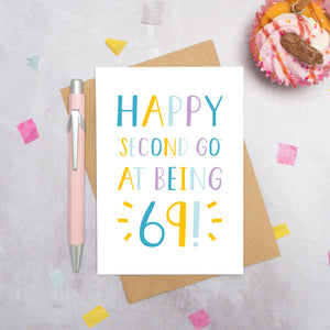 Happy second go at being 69 - milestone age card in blue, yellow and purple photographed on a grey background surrounded by a cupcake, pen and confetti.