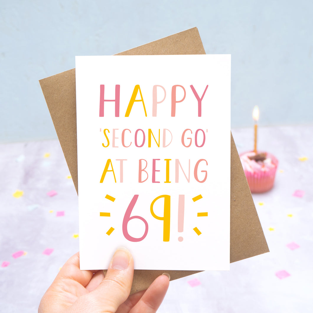 Happy second go at being 69 - milestone age card in pink photographed on a grey and blue background with a cupcake and burning candle.