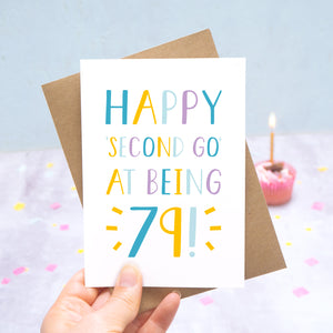 Happy second go at being 79 - milestone age card in blue, yellow and purple photographed on a grey and blue background with a cupcake and burning candle.