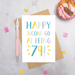 Happy second go at being 79 - milestone age card in blue, yellow and purple photographed on a grey background surrounded by a cupcake, pen and confetti.