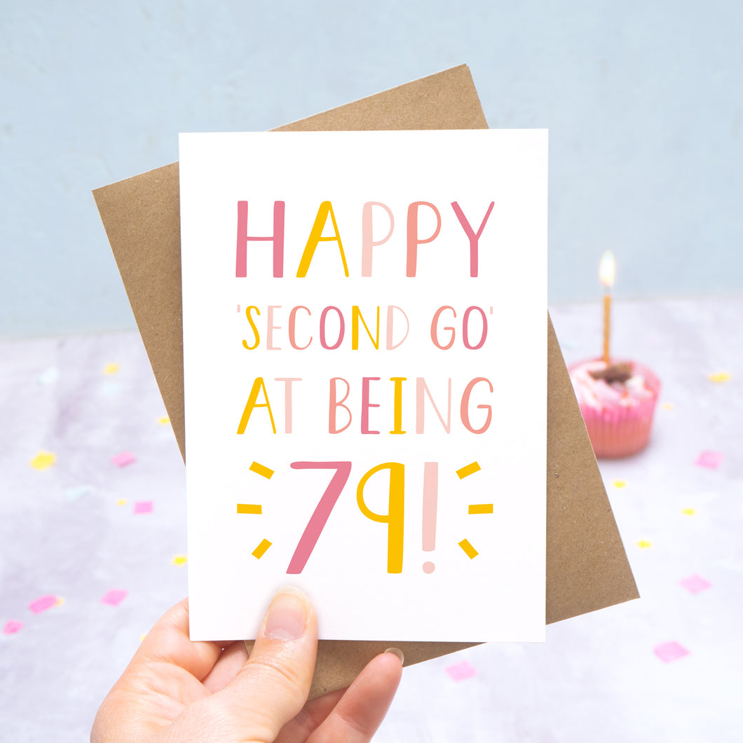 Happy second go at being 79 - milestone age card in pink photographed on a grey and blue background with a cupcake and burning candle.