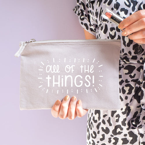 All of the things cotton pouch in grey with white text. Shot on a lilac background. Model wears leopard print whilst holding the pouch with a lipstick.