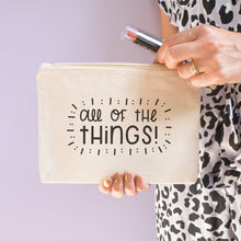 Load image into Gallery viewer, All of the things cotton pouch in natural with black text. Shot on a lilac background. Model wears leopard print whilst holding the pouch with a lipstick.