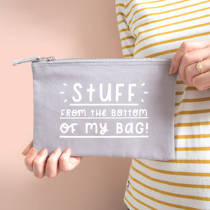Stuff from the bottom of my bag cotton pouch in grey with white text. Shot on a peach background with two hands holding the pouch and model wears yellow and white stripy top