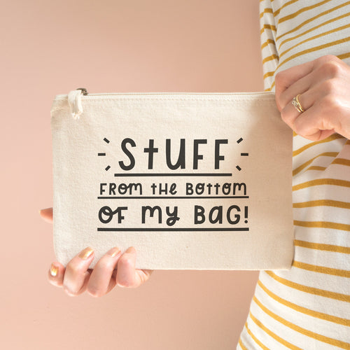Stuff from the bottom of my bag cotton pouch in natural with black text. Shot on a peach background with two hands holding the pouch and model wears yellow and white stripy top