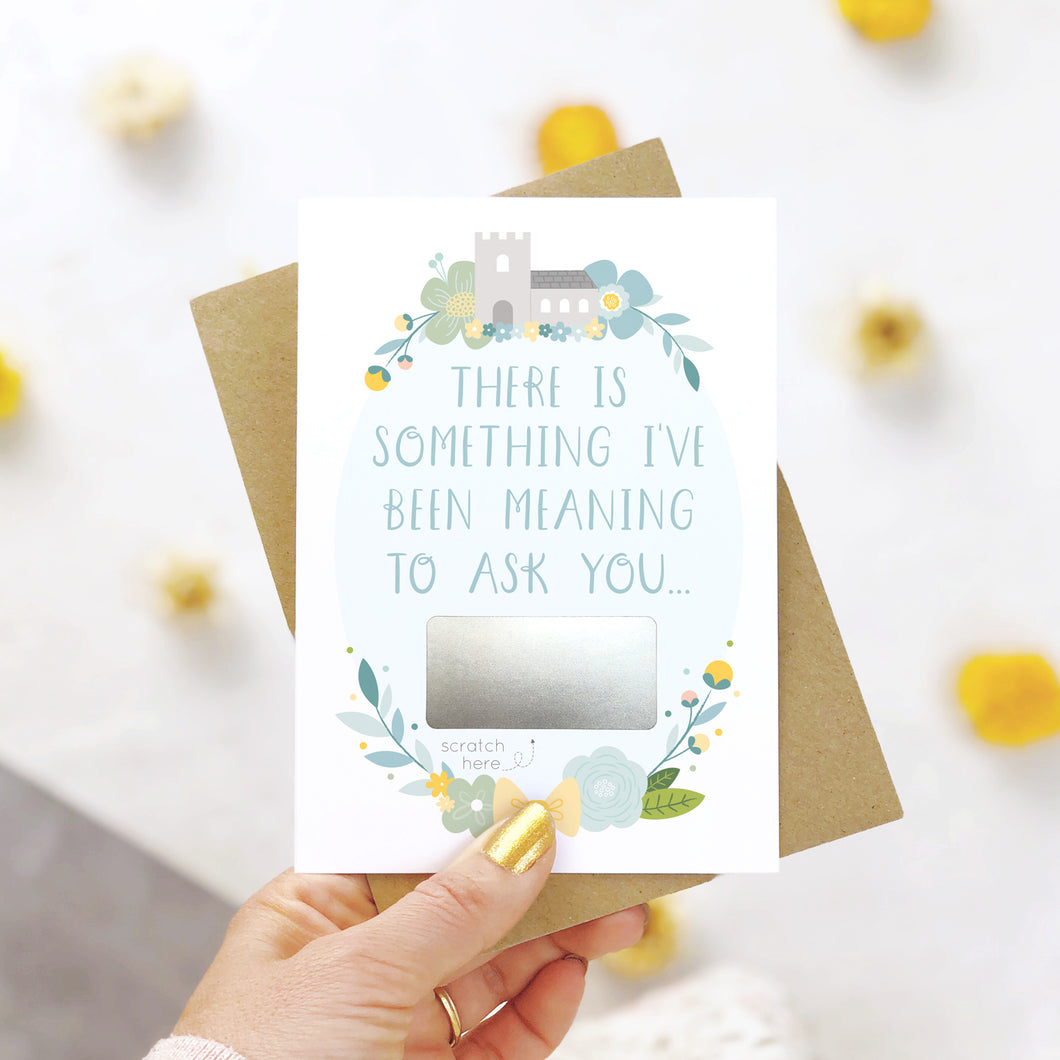 A will you be my godparents scratch and reveal card being held over a white background with pops of yellow. The design features a church, simple florals and a scratch off panel in silver. This is the blue palette.