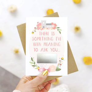 A will you be my godparents scratch and reveal card being held over a white background with pops of yellow. The design features a church, simple florals and a scratch off panel in silver. This is the pink palette.