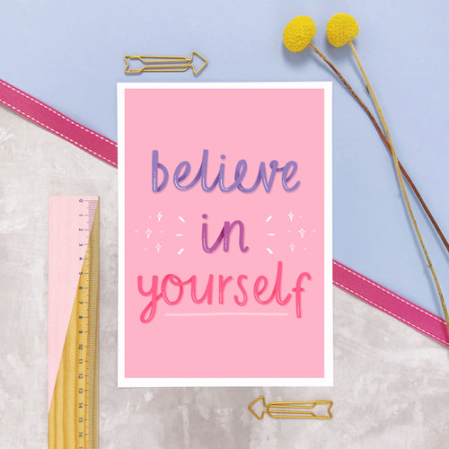 Believe in yourself A5 print featuring a pink background, with a white border and hand lettering in purple and dark pink. The print is sat on a marble and lilac background surrounded with photography props.