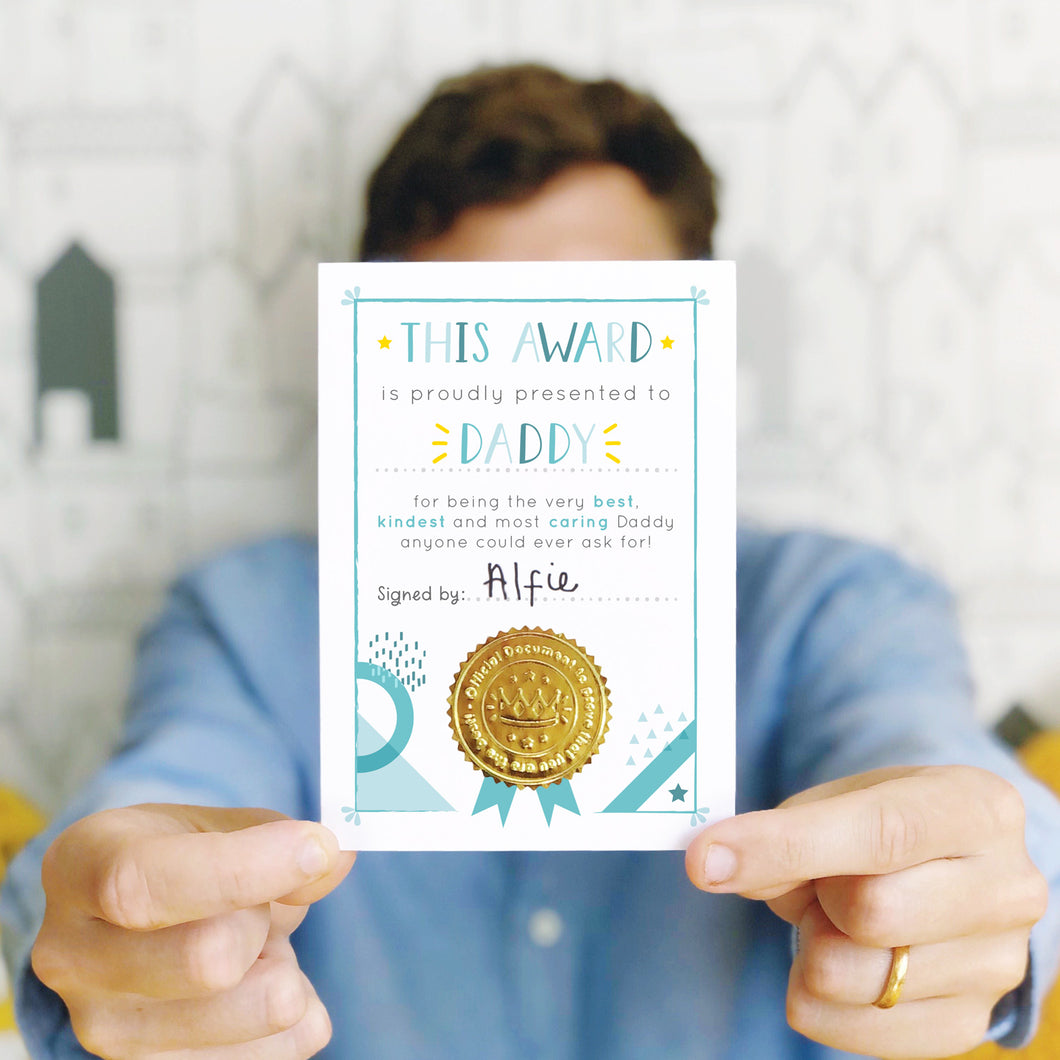 Best Daddy award printed on white card in tones of blue and yellow. There is also a gold, shiny, certificate seal on the bottom. This Father's Day card is being held by a man in a blue shirt against a white background