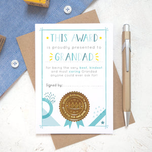 A Grandad certificate award card printed onto white card in varying tones of blue and pops of yellow! Each card features a shiny gold seal to make it official! Photographed on a white background with a hint of a blue shirt and a brown kraft envelope.