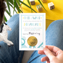 Load image into Gallery viewer, A Grandad certificate award card printed onto white card in varying tones of blue and pops of yellow! Each card features a shiny gold seal to make it official! Photographed over a lap with a yellow footrest in the background.